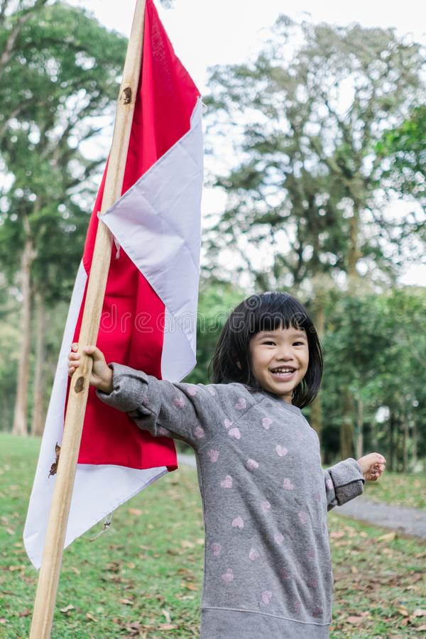 Asian little girl flapping Indonesian flag. With spirit in the park royalty free stock photo