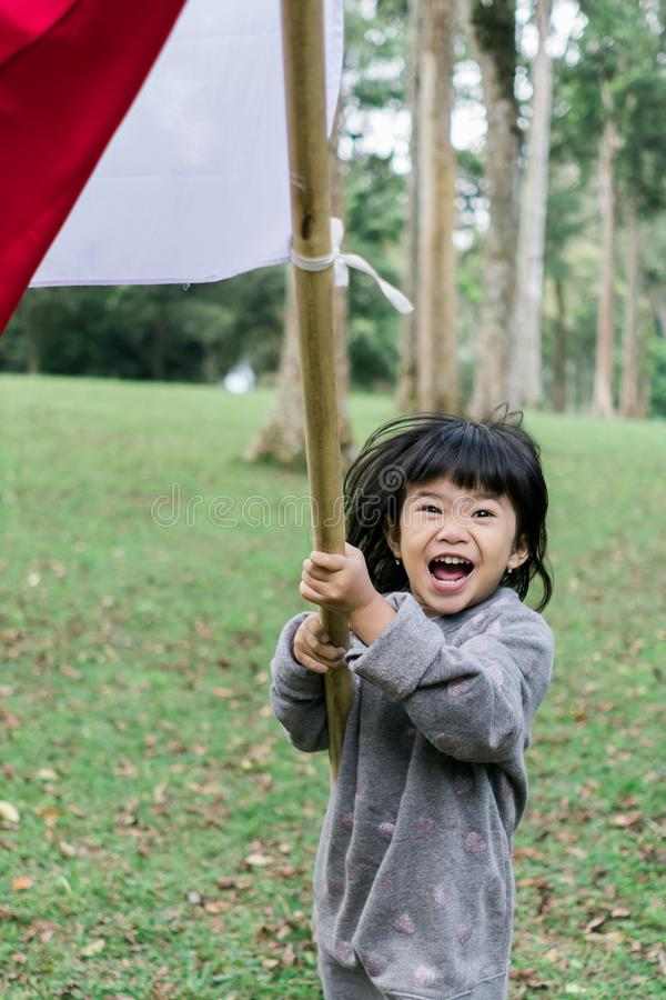 Asian little girl flapping Indonesian flag. With spirit in the park stock photos