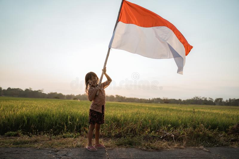 Asian little girl flapping Indonesian flag. With spirit in the rice field stock photos
