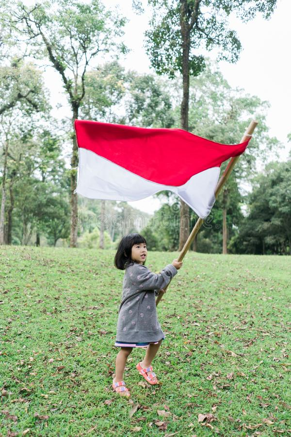 Asian little girl flapping Indonesian flag. With spirit in the park stock photography