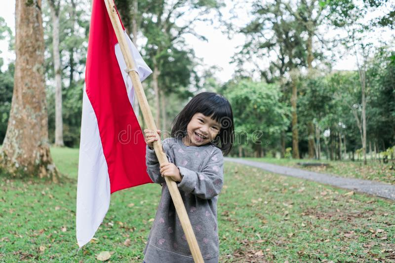 Asian little girl flapping Indonesian flag. With spirit in the park royalty free stock photos
