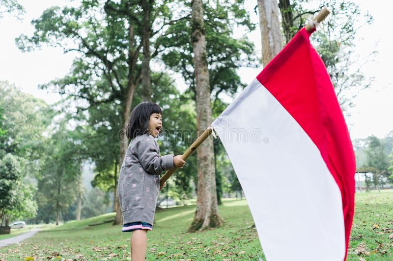 Asian little girl flapping Indonesian flag. With spirit in the park royalty free stock photography