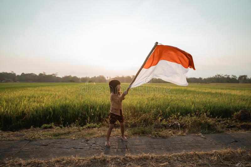 Asian little girl flapping Indonesian flag. With spirit in the rice field royalty free stock images