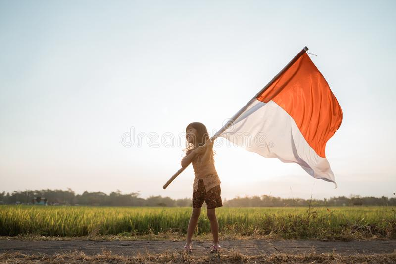 Asian little girl flapping Indonesian flag. With spirit in the rice field stock photo
