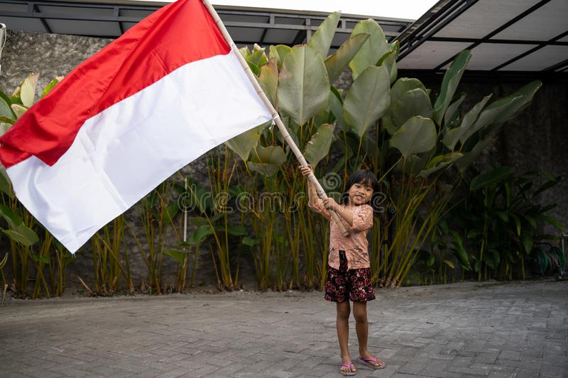 Asian little girl flapping Indonesian flag. With spirit at yard home stock photography