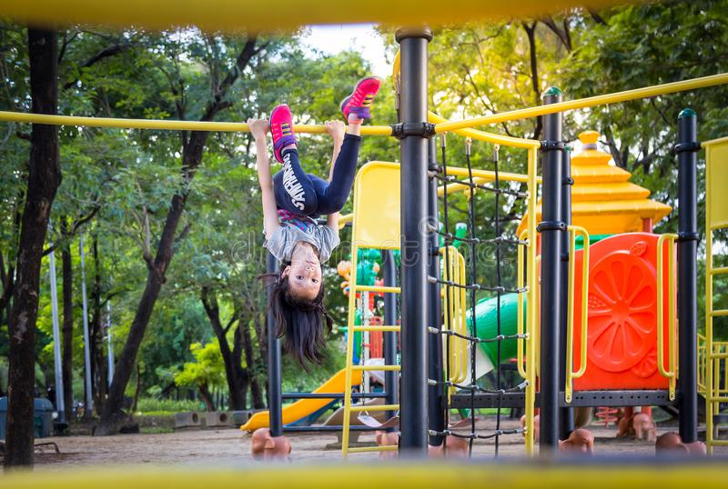 Asian little girl is hanging upside down on a playground outdoor and looking at camera in the park,summer,vacation concept royalty free stock photography