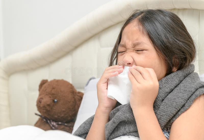 Asian little girl has runny nose and blows nose into tissue. Sick child. Asian little girl has runny nose and blows nose into tissue lying with her bear on bed stock photography