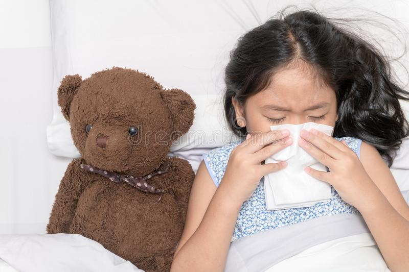 Asian little girl has runny nose and blows nose into tissue. Sick child. Asian little girl has runny nose and blows nose into tissue lying with her bear on bed stock images