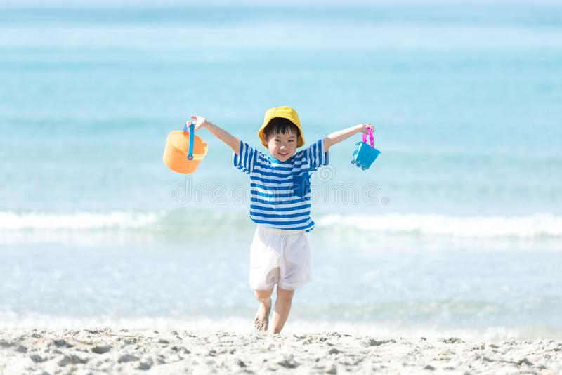 Asian little girl have fun and play yellow ball on the beach.  Family kid tourism travel enjoy and freedom in summer and holiday f. Or leisure and destination stock image