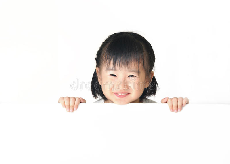Asian little girl hiding behind white board. Asian little girl smile and hiding behind a blank white board royalty free stock images