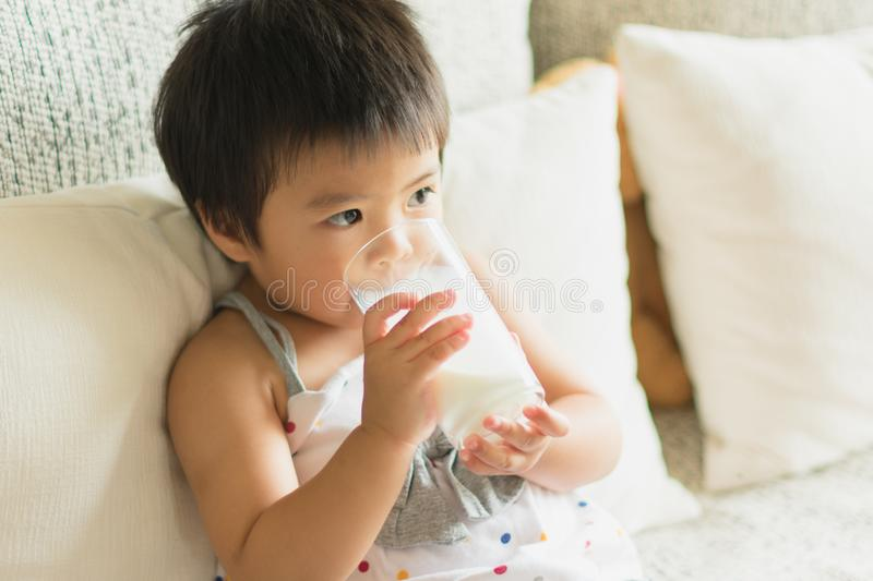 Asian little girl is holding and drinking a glass of milk in living room stock photo
