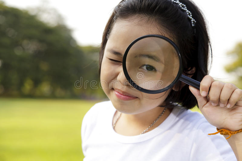 Girl holding a magnifying glass royalty free stock photo