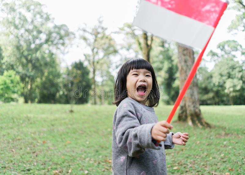Asian little girl holding a stick of Indonesian flag with toothy. Asian little girl holding a stick of Indonesian flag when look at at camera with toothy stock photos