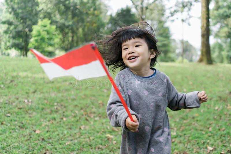 Asian little girl holding a stick of Indonesian flag with toothy. Asian little girl holding a stick of Indonesian flag when look at at camera with toothy royalty free stock images