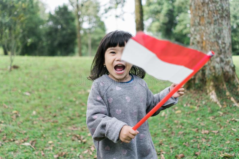 Asian little girl holding a stick of Indonesian flag with toothy. Asian little girl holding a stick of Indonesian flag when look at at camera with toothy stock image