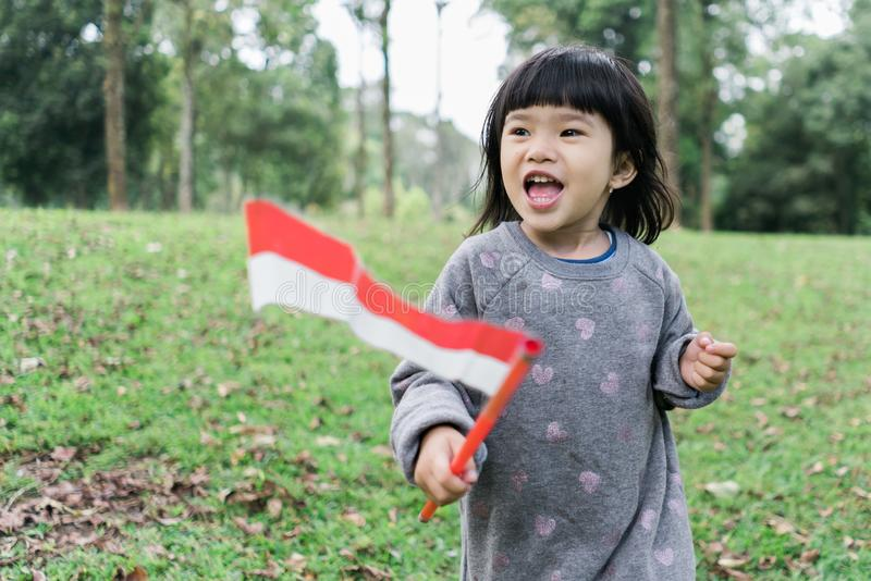 Asian little girl holding a stick of Indonesian flag with toothy. Asian little girl holding a stick of Indonesian flag when look at at camera with toothy stock photo