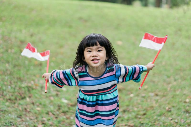 Asian little girl holding two stick of flag with toothy. Asian little girl holding two stick of flag when look at at camera with toothy royalty free stock photos