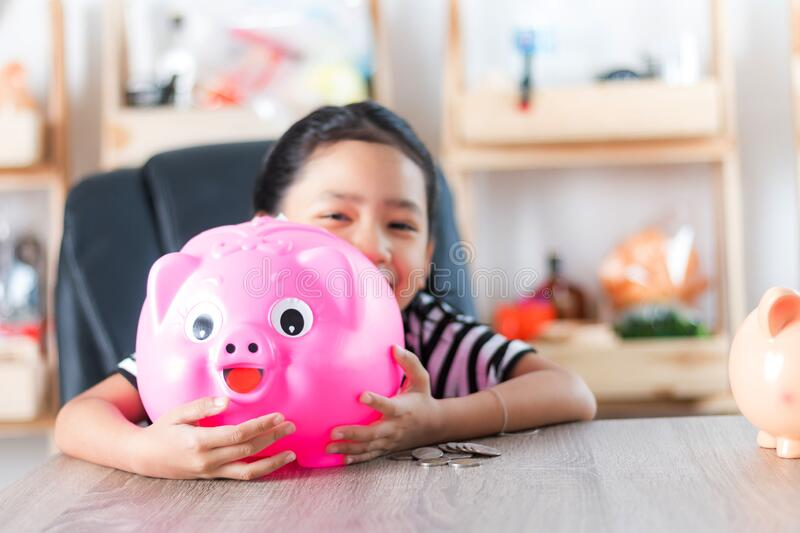 Asian little girl in hugging piggy bank shallow depth of field select focus. At the pig stock photography