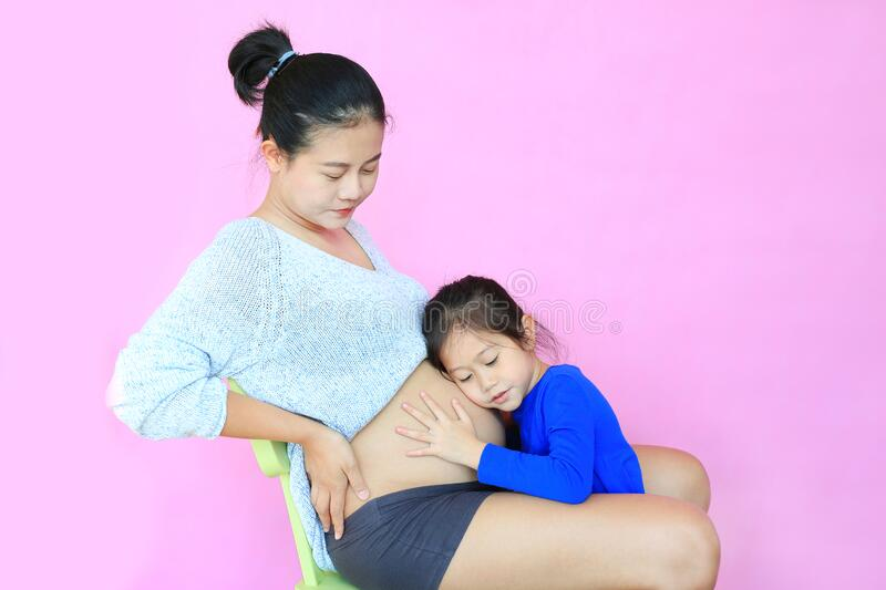 Asian little girl listening baby in belly of pregnant mother isolated on pink background. Pregnancy and new life concept royalty free stock images