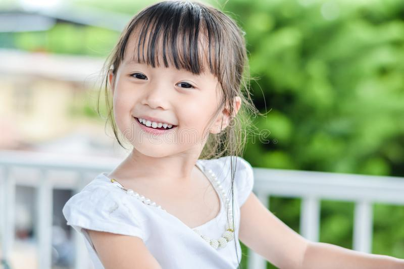Asian little girl outdoors with smiley face feeling relax be happy in good day royalty free stock image