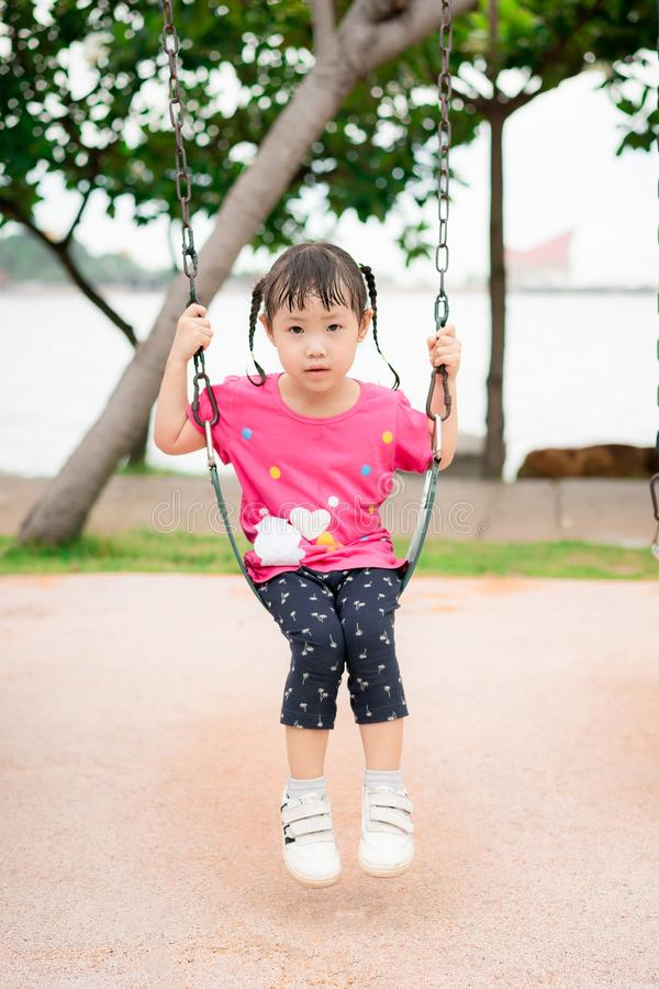 Asian little girl play on a swing at the park, little girl have fun and happy stock photography