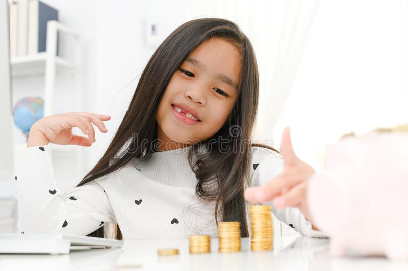 Asian little girl playing with coins making stacks of money,kid saving money for the future concept stock images