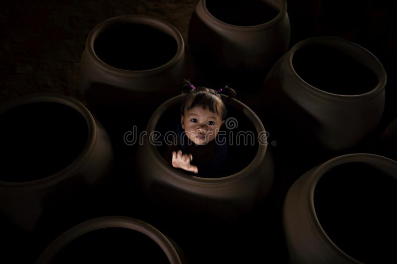 Asian little girl playing in earthenware. stock photo