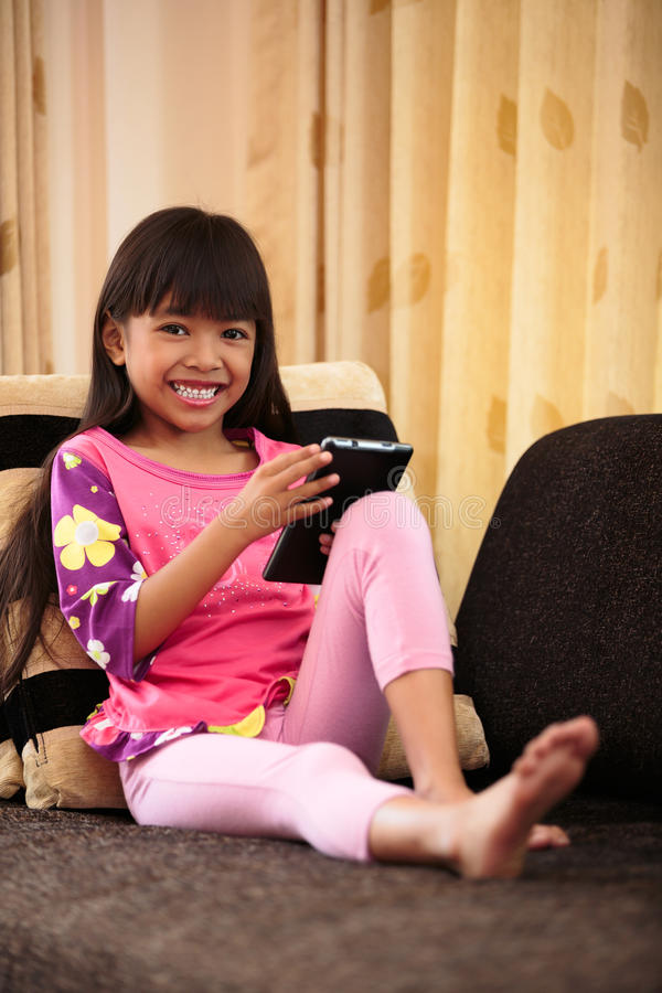 Download Asian Little Girl Playing With Tablet At Home Stock Photo - Image: 29973896