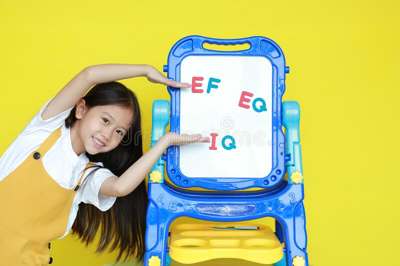 Asian little girl present something on white board for study in class. Schoolgirl present text EF, EQ and IQ on whiteboard on royalty free stock photos