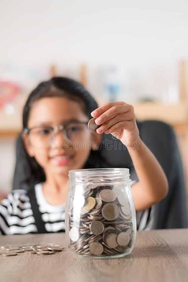 Asian little girl in putting coin in to glass jar shallow depth of field select focus at the hand. Bank, piggy, money, kid, child, children, kids, savings royalty free stock image