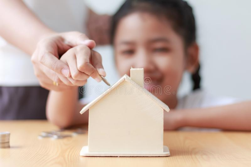 Asian little girl putting coin to house piggy bank shallow depth royalty free stock photo