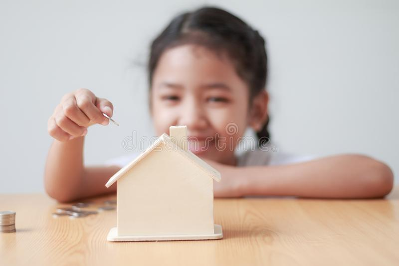 Asian little girl putting coin to house piggy bank shallow depth. Of field select focus on hand stock photos