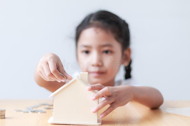 Asian little girl putting coin to house piggy bank shallow depth. Of field select focus on house royalty free stock photography