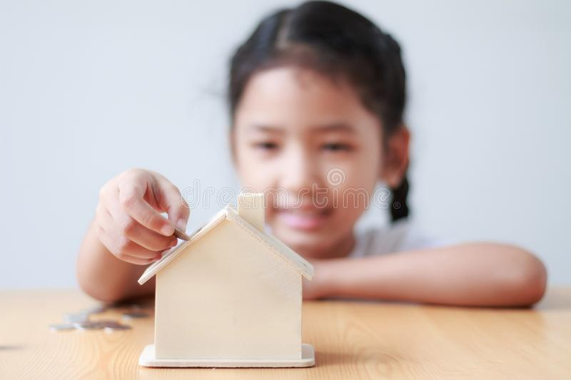 Asian little girl putting coin to house piggy bank shallow depth. Of field select focus on house royalty free stock image