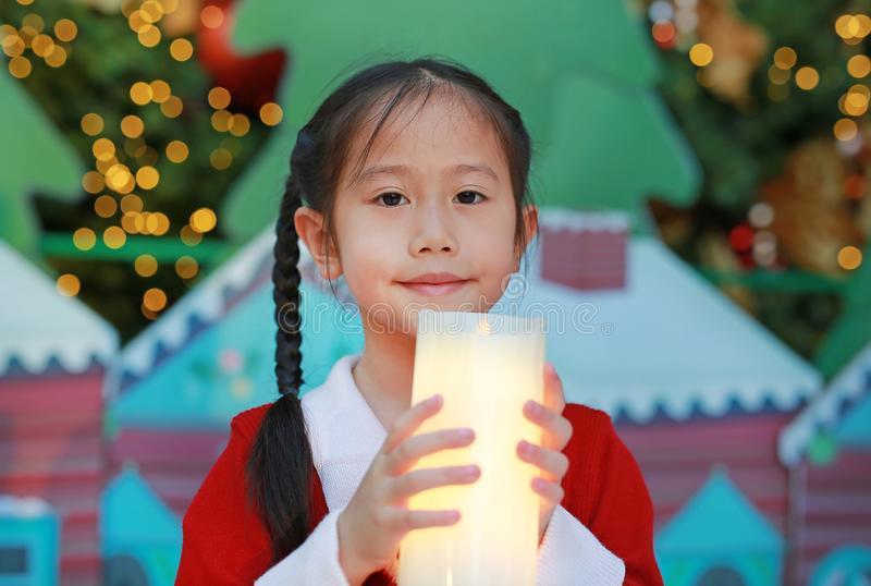 Asian little girl in red dress holding a candle against christmas background in the winter season and happy new year festival.  royalty free stock photography