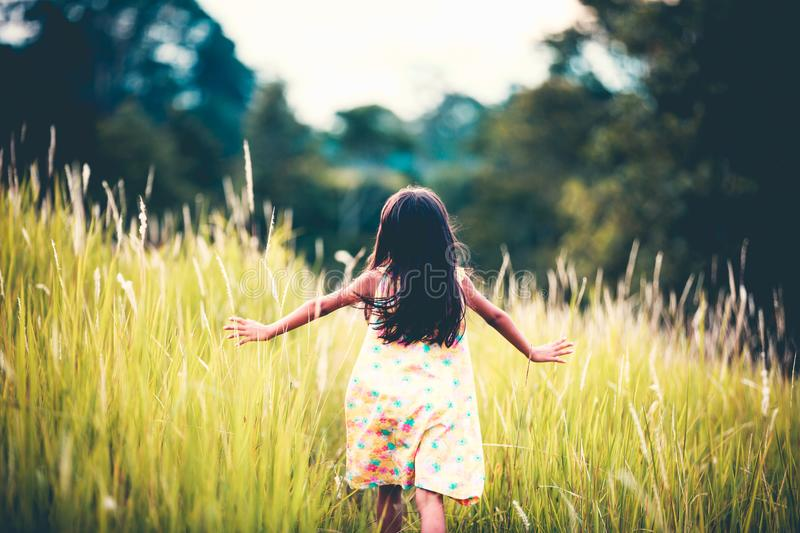 Asian little girl running away. In a field outdoors, Vintage color tone royalty free stock image