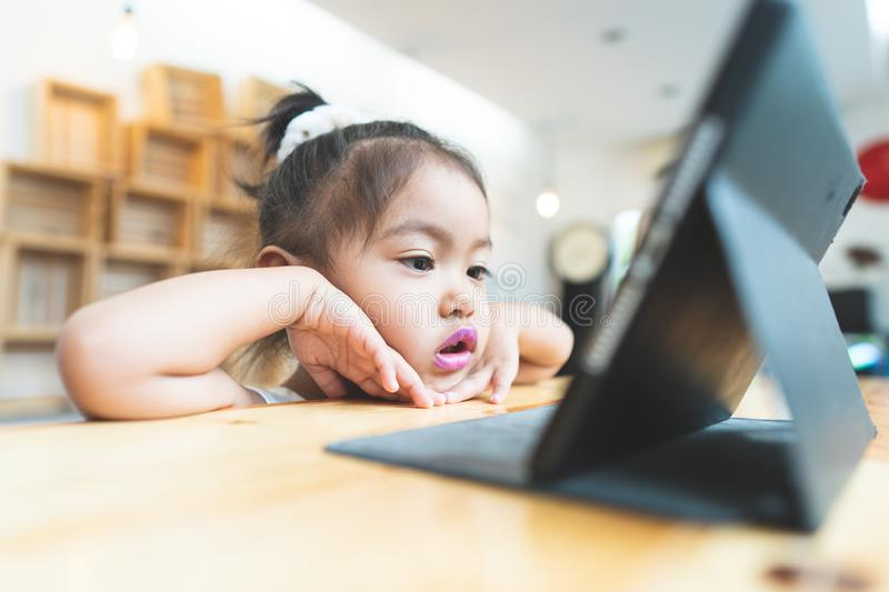 Asian little girl Sitting Tablet at home stock photography