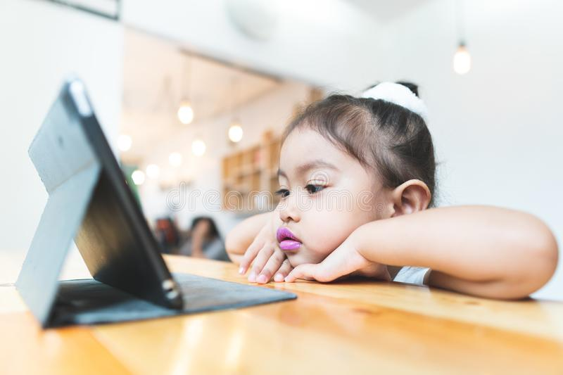 Asian little girl Sitting Tablet at home. royalty free stock image
