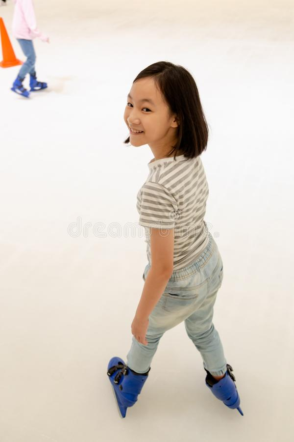 Asian little girl on the skating rink in blue ice skates,smile happily cute child play ice skating in shopping mall outlets, royalty free stock photos