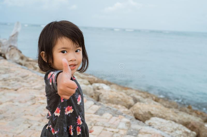 Asian little girl standing in the beachline and look back with thumb up to the camera royalty free stock images