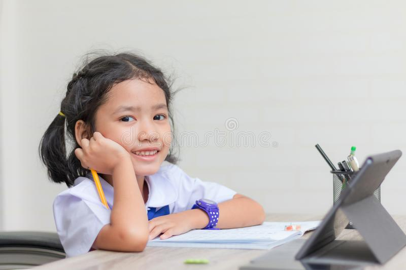 Asian little girl in student uniform doing homework and using tablet on wooden table select focus shallow depth of field stock photos
