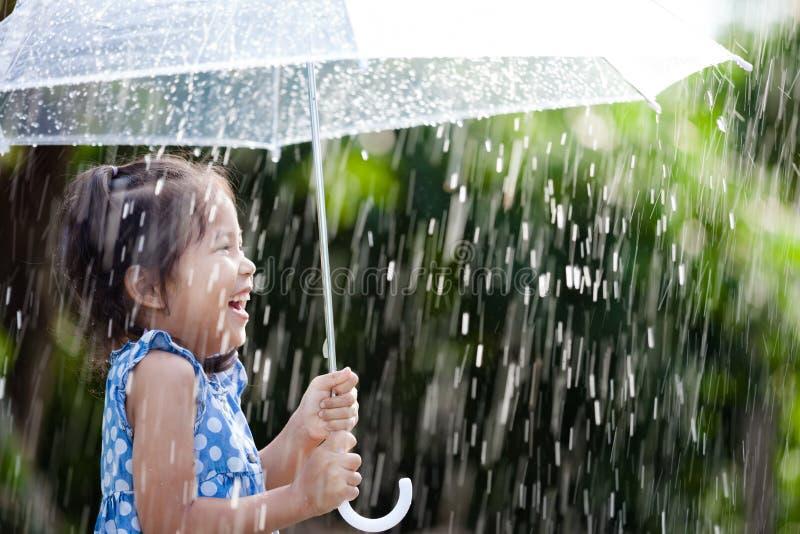 Asian little girl with umbrella in rain. Happy asian little girl with umbrella in rain stock photography