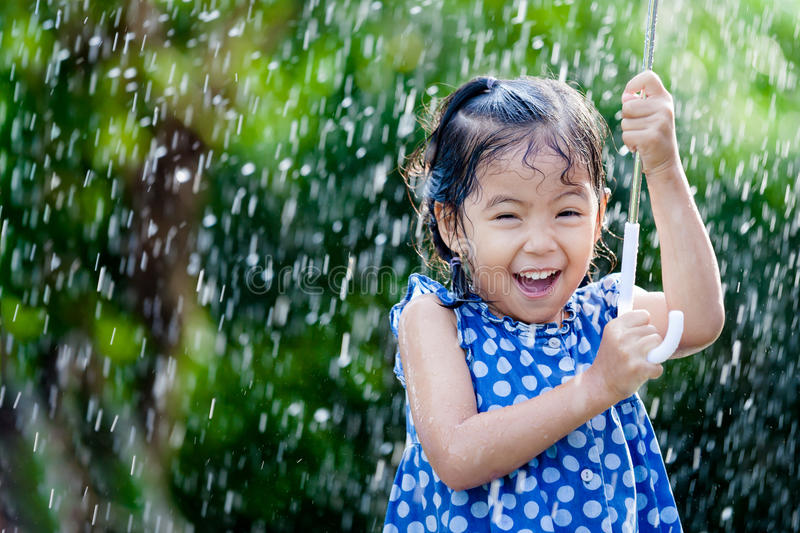 Asian little girl with umbrella in rain royalty free stock photography