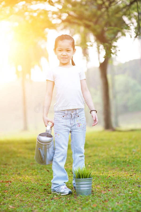 Asian little girl watering plant outdoors. royalty free stock images
