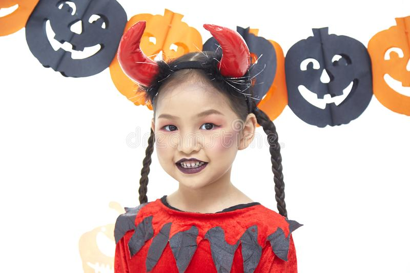 Asian little girl is wearing red devil costume stock photography