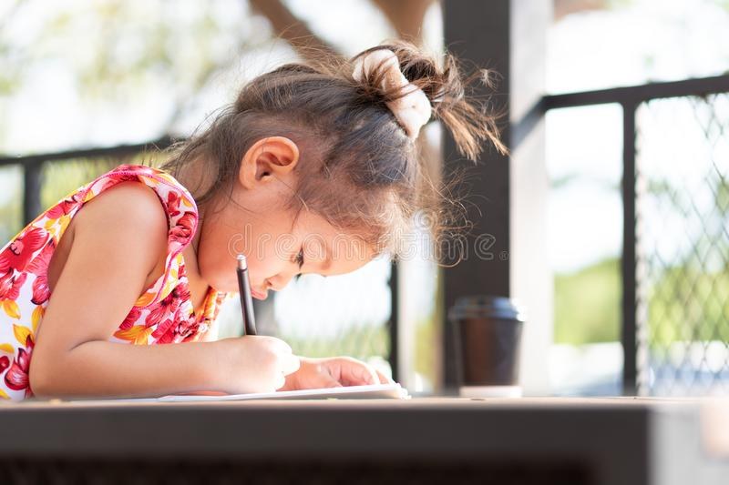 Little girl is writing a book in the morning atmosphere stock photos