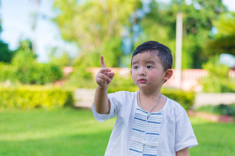 Asian little Kid pointing up by fingers to something or empty co stock image