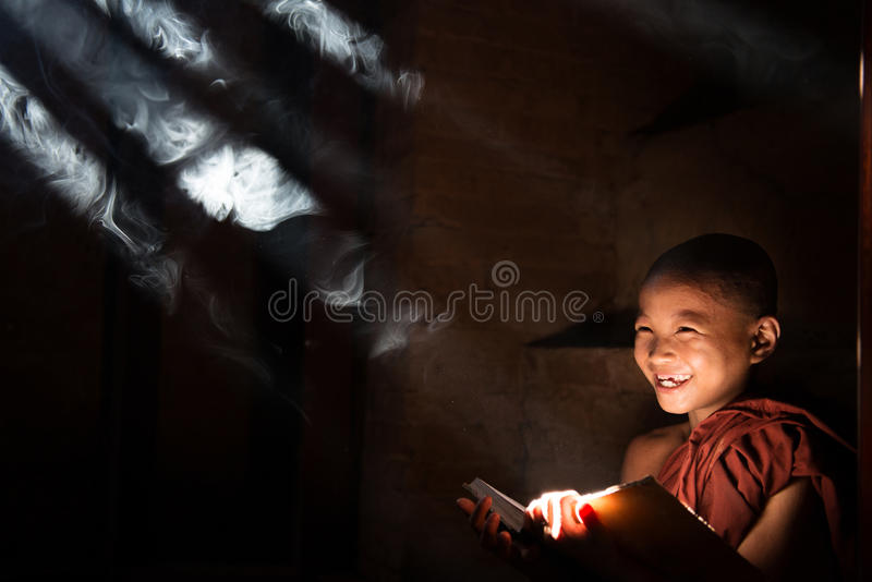 Asian little monk reading book stock images