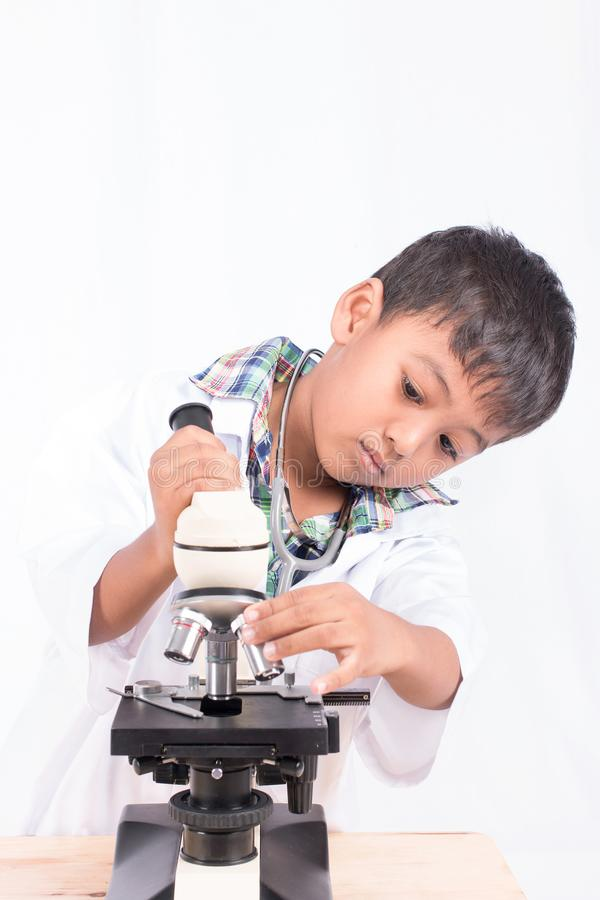 asian little student boy working with microscope stock photography