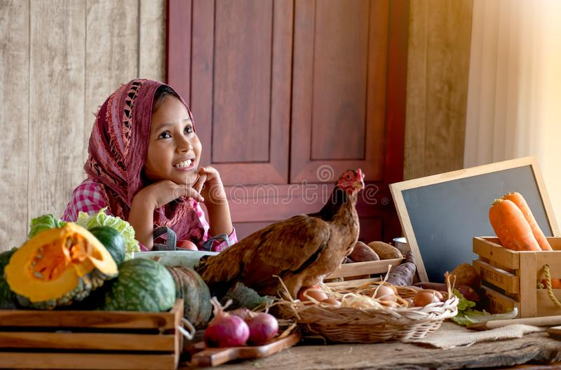 Asian little young girl look forward and smile among various types of vegetable on the table in her kitchen.  royalty free stock image